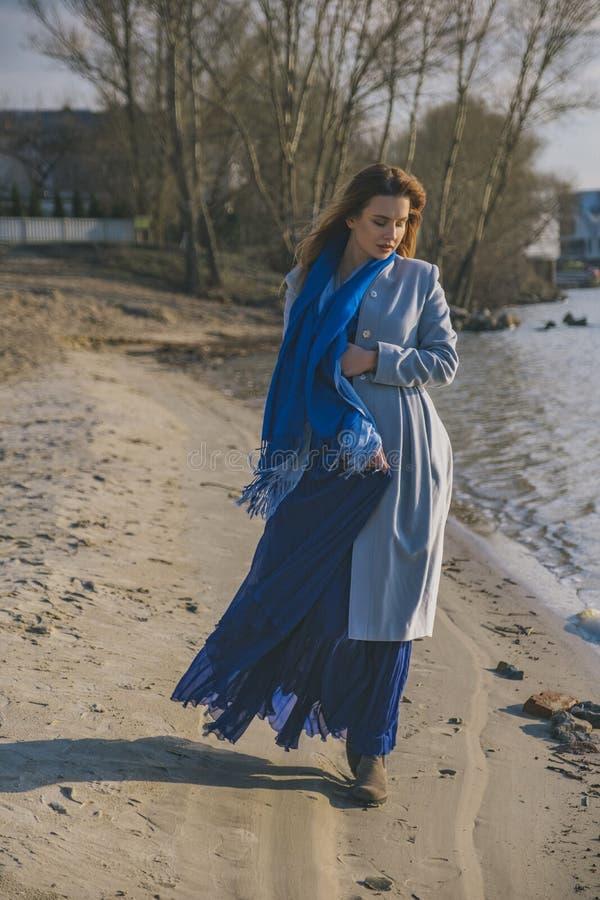 Mulher europeia lindo no revestimento e no vestido mornos em uma caminhada no parque perto do rio Tempo ventoso Sua roupa voa no  imagens de stock royalty free
