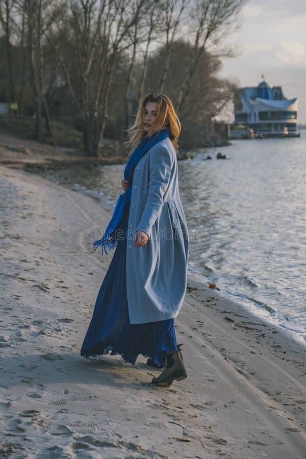 Mulher europeia lindo no revestimento e no vestido mornos em uma caminhada no parque perto do rio Tempo ventoso Sua roupa voa no  imagem de stock