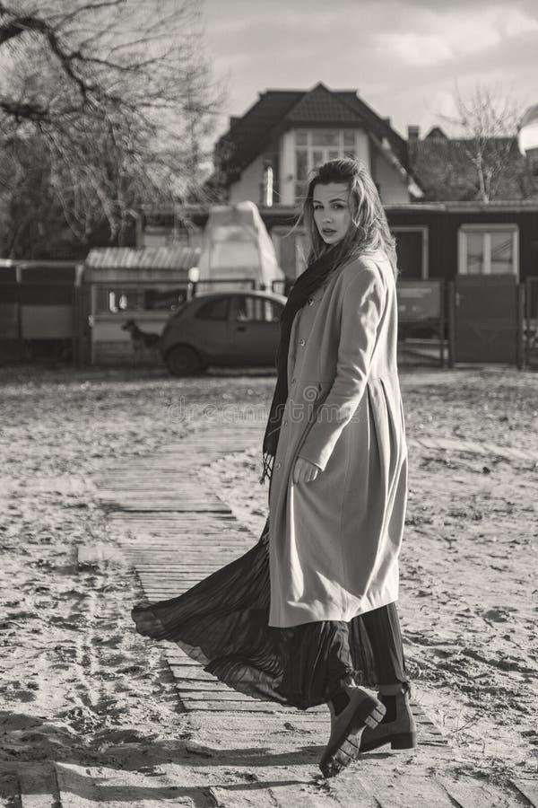 Mulher europeia lindo no revestimento e no vestido mornos em uma caminhada no parque perto do rio Tempo ventoso Sua roupa voa no  imagens de stock