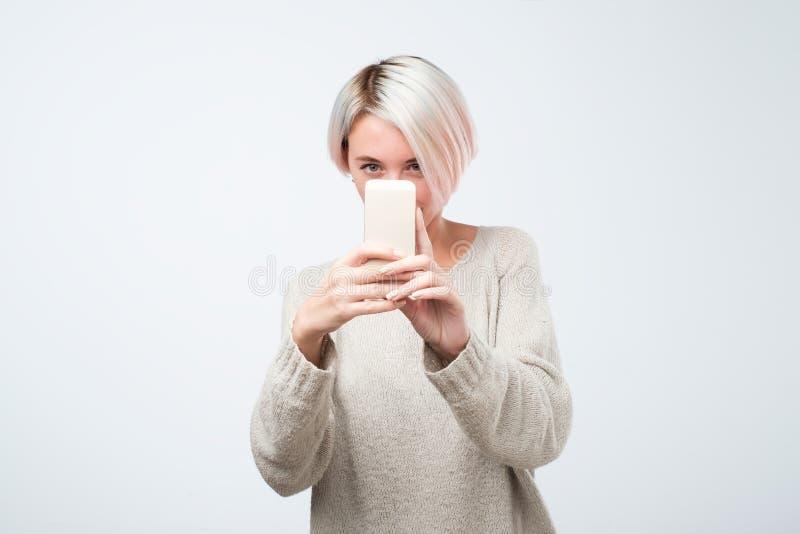 A mulher europeia nova com cabelo tingido curto está tomando a foto em um smartphone fotos de stock