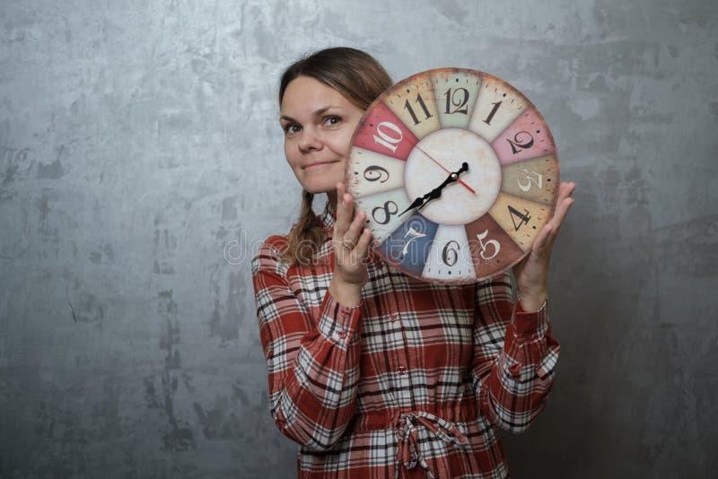 Mulher europeia nova no vestido da manta que guarda o relógio redondo do vintage imagem de stock royalty free