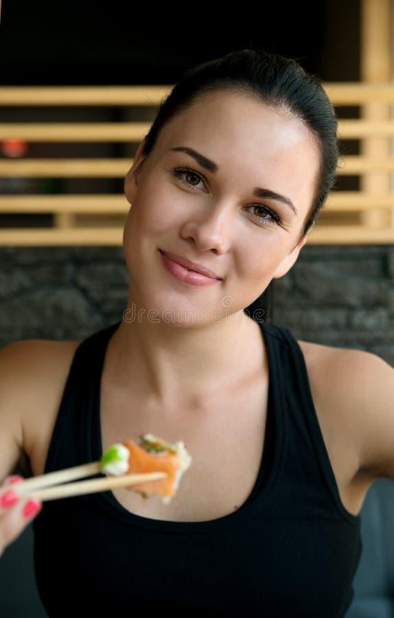 Mulher europeia nova que come o sushi em um restaurante asiático imagem de stock
