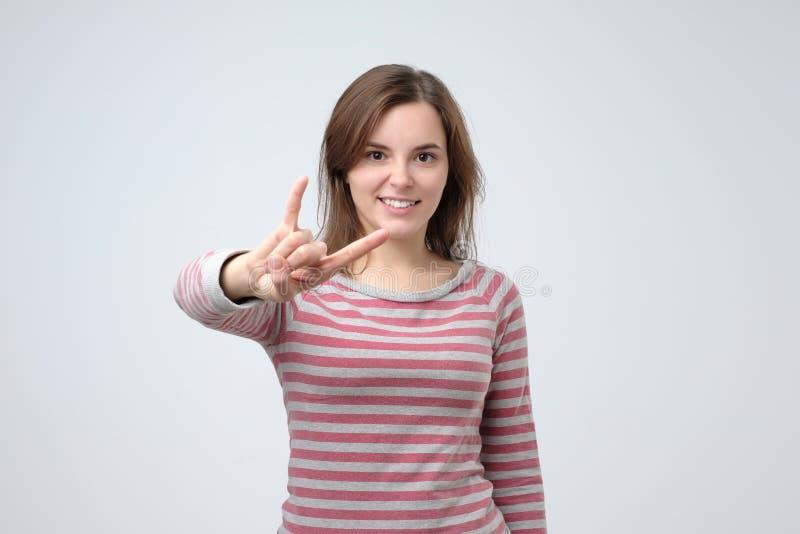 Mulher europeia nova que mostra o gesto de mão do rock and roll que levanta no estúdio fotografia de stock royalty free