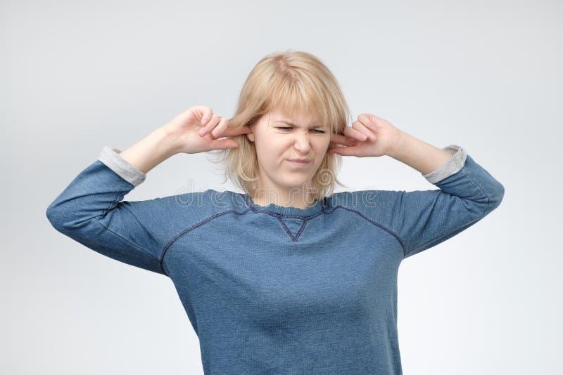 Mulher europeia nova que obstrui as orelhas, olhando acima, fingindo não se ouvir o que é dita foto de stock royalty free