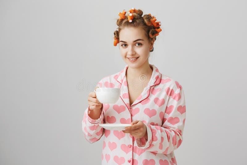 Mulher europeia ordinária bonita em encrespadores e em pyjamas de cabelo, guardando o copo ao beber o café ou o chá na manhã, sor fotos de stock