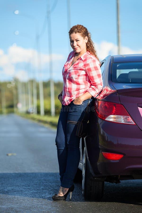 Mulher europeia vestida em suportes da camisa e das calças de brim na borda da estrada antes do carro estacionado, retrato comple foto de stock