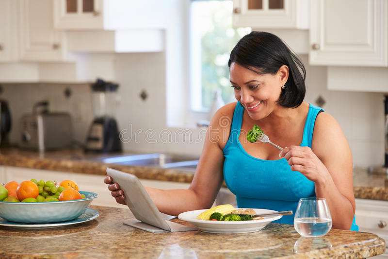 Mulher excesso de peso com tabuleta de Digitas que verifica a entrada da caloria foto de stock