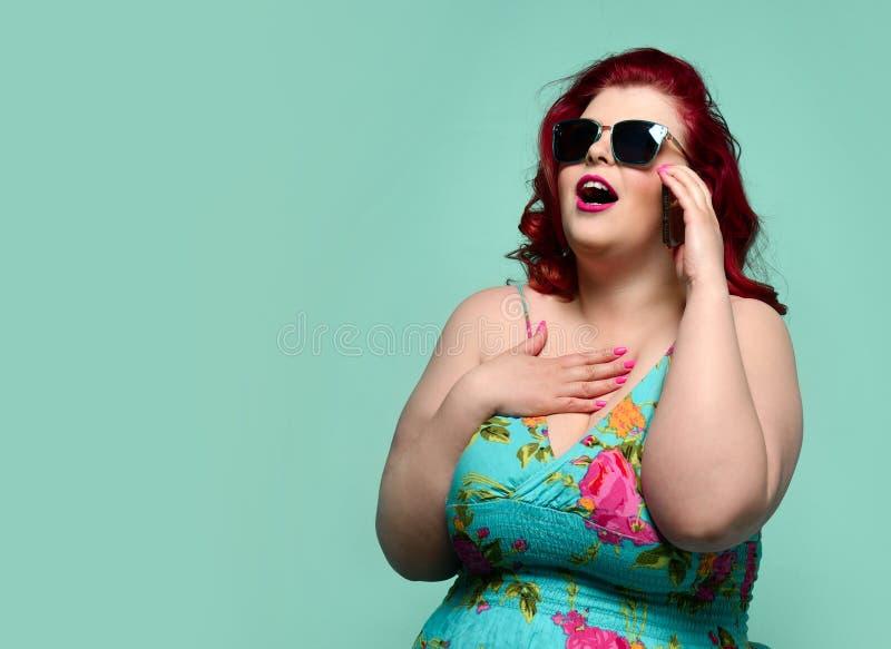 mulher excesso de peso da senhora do Mais-tamanho nos óculos de sol e negociações coloridas dos sundress no telefone celular e pa fotos de stock royalty free