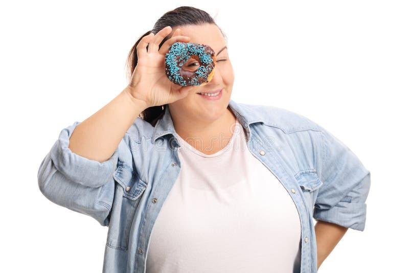 Mulher excesso de peso que espreita o thrugh uma filhós do chocolate fotos de stock royalty free