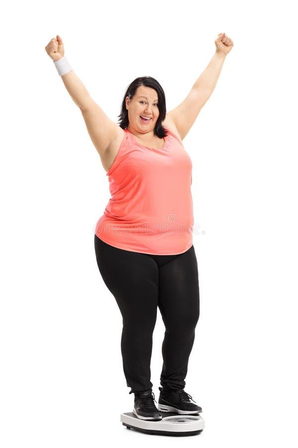 Mulher excesso de peso que está em uma escala do peso e que gesticula o happin fotos de stock