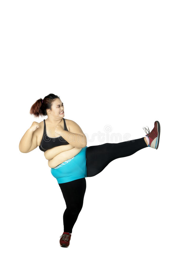 Mulher excesso de peso que executa um pontapé imagens de stock