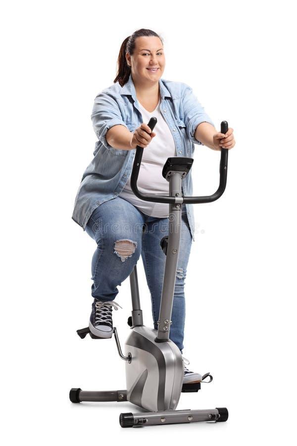 Mulher excesso de peso que exercita em uma bicicleta estacionária imagem de stock royalty free