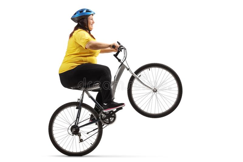 Mulher excesso de peso que monta uma bicicleta e que faz um wheelie imagens de stock