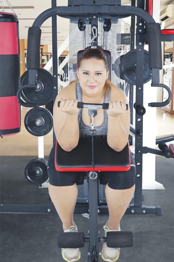 Mulher excesso de peso que usa uma máquina do gym imagens de stock