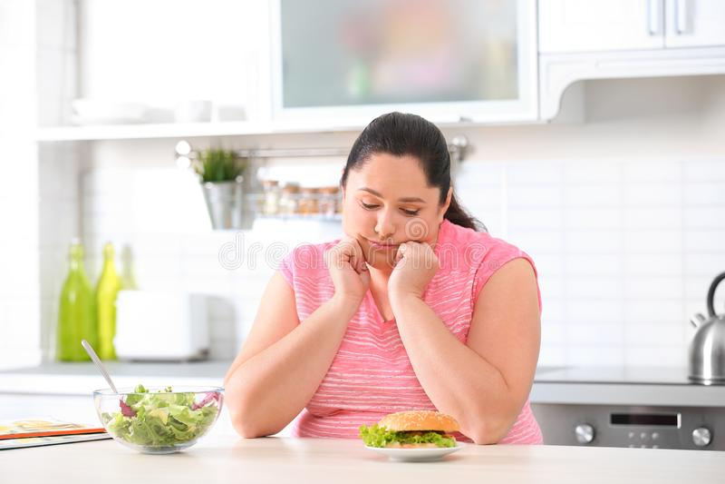 Mulher excesso de peso triste que escolhe entre a salada e o hamburguer na cozinha fotografia de stock royalty free