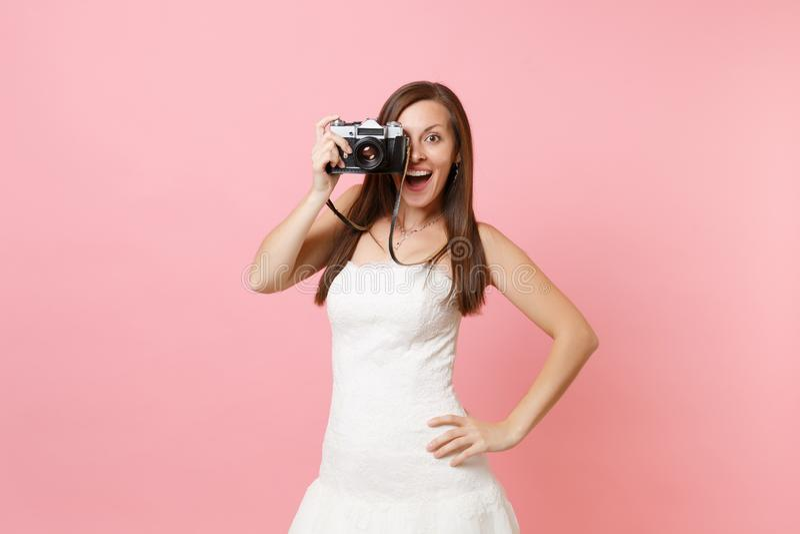 A mulher excitada da noiva no vestido de casamento toma imagens na câmera retro da foto do vintage, escolhendo o pessoal, fotógra fotografia de stock