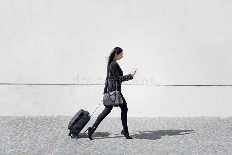A mulher executiva e moderna anda a rua com seu whi da bagagem fotos de stock