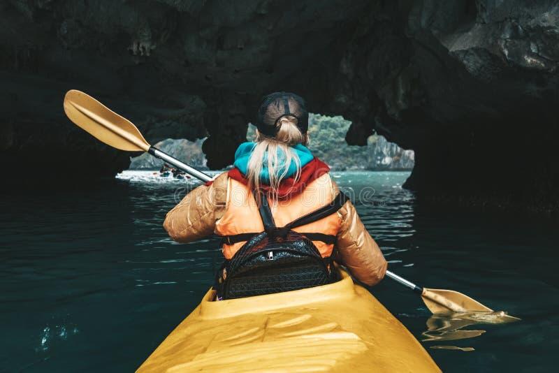 A mulher explora e remando o caiaque dentro da caverna do cársico na baía longa do Ha VietnamMountains e caverna do mar, curso a  fotografia de stock