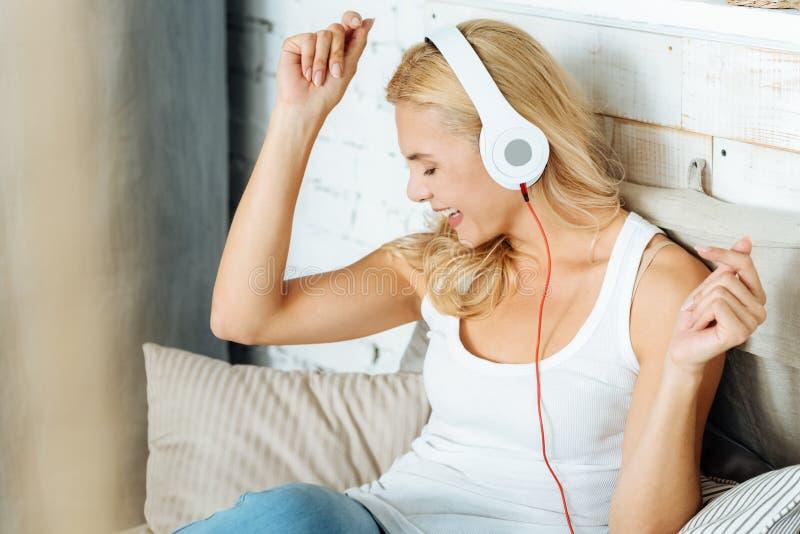 Mulher extático que escuta a música na cama imagem de stock royalty free