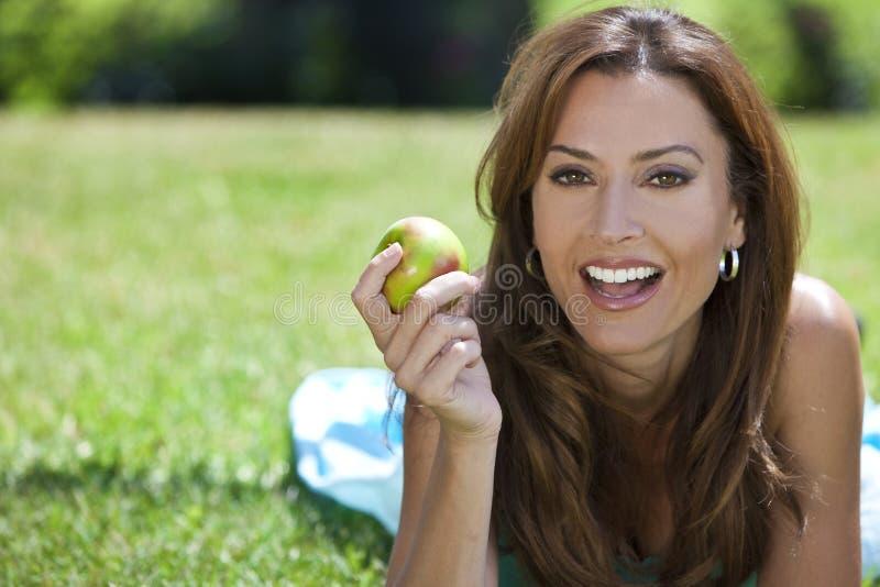 Mulher exterior comendo um Apple & um sorriso fotos de stock