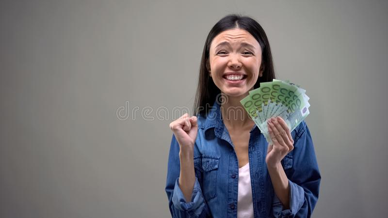 Mulher extremamente feliz que guarda cédulas dos euro, bom salário, conceito do emprego fotos de stock