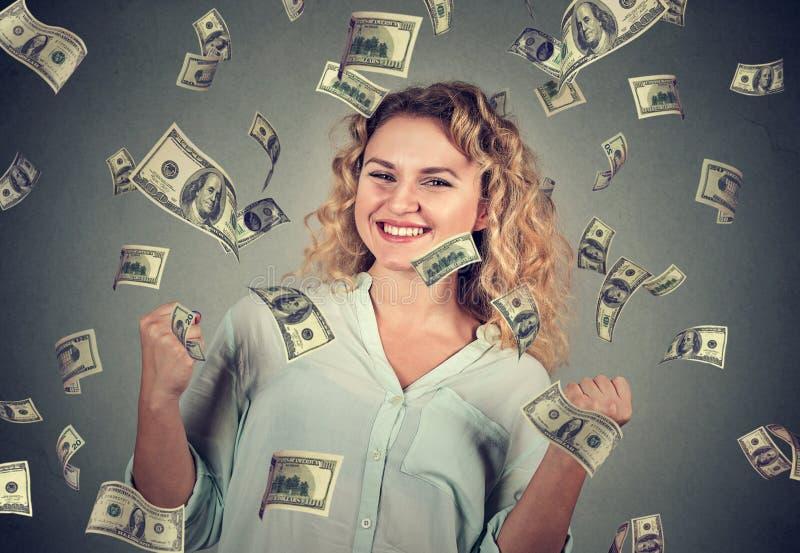 A mulher exulta os punhos de bombeamento comemora o sucesso sob a chuva do dinheiro imagem de stock royalty free