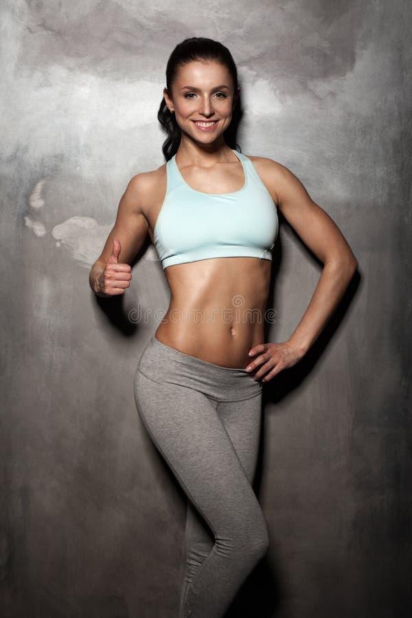 A mulher fêmea da aptidão com corpo muscular, exercício com, Abs, abdominals, mostrando manuseia acima do gesto imagem de stock