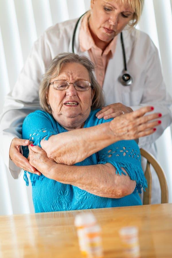 Mulher f?mea do doutor Helping Senior Adult com exerc?cios de bra?o fotografia de stock