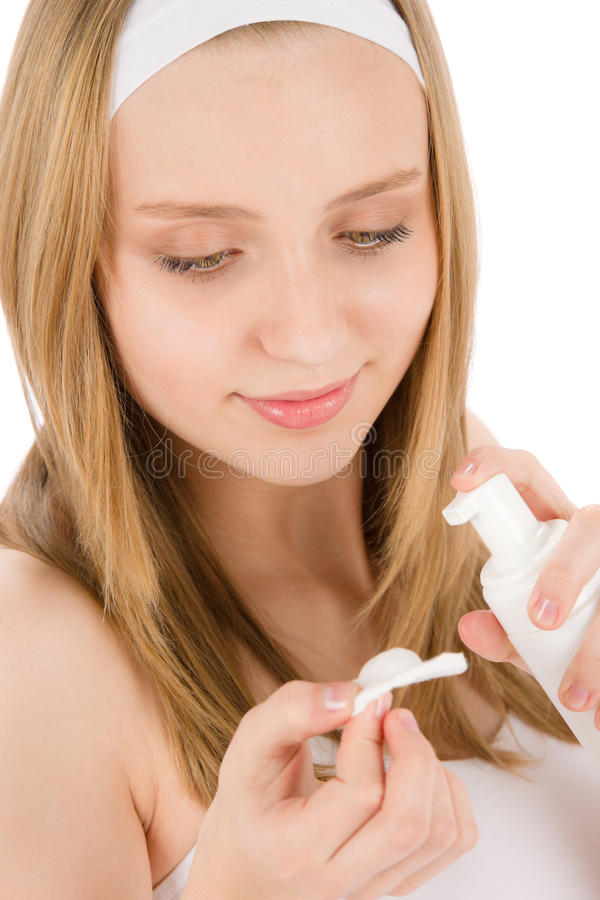 A mulher facial do adolescente do cuidado da acne aplica o creme fotos de stock