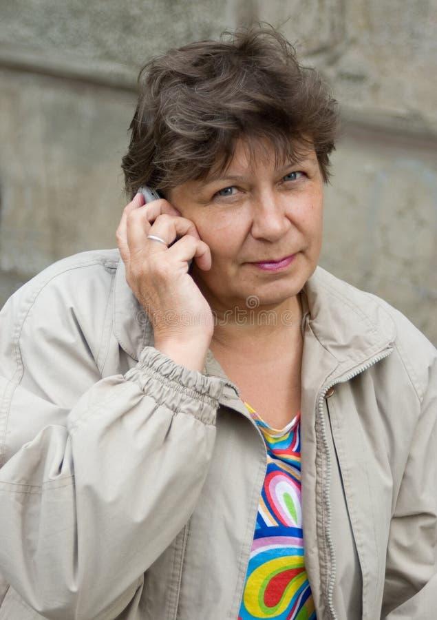 A mulher fala no telefone fotografia de stock royalty free