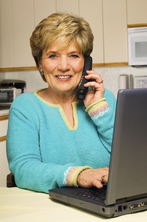 A mulher fala no telefone ao trabalhar no portátil fotografia de stock royalty free