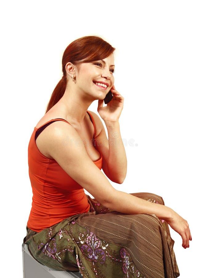 A mulher fala pelo telefone celular preto fotografia de stock royalty free