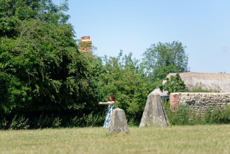 A mulher faz alguma ioga transporta-se próximo às pedras monolíticas, avebury imagem de stock royalty free