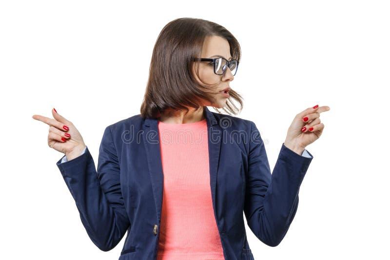 A mulher faz a escolha, fêmea adulta com os vidros que vestem o revestimento que mostra suas mãos em sentidos diferentes Fundo br imagens de stock royalty free