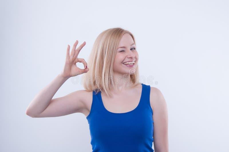 A mulher faz está bem, bom sinal com sua mão e irradiação fotografia de stock