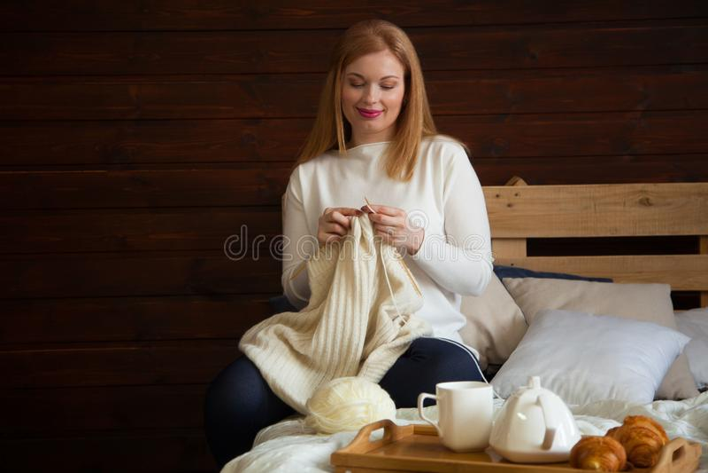 A mulher faz malha a roupa de lã Agulhas de confecção de malhas Close-up Natu fotografia de stock