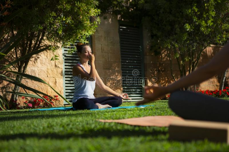 A mulher faz o exercício da ioga no parque fotografia de stock