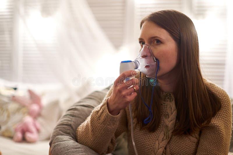 A mulher faz o nebulizer da inala??o em casa guardando um nebulizer da m?scara que inala emana??es pulverize a medicamenta??o em  fotografia de stock