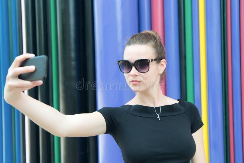 A mulher faz o selfie com o smartphone em Paris, france Mulher com telefone celular no fundo colorido Menina nos óculos de sol co imagem de stock