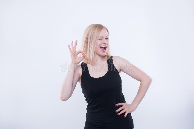 A mulher faz o sinal aprovado com suas mão e irradiação Expressão facial expressivo e emoção Retrato do sorriso louro bonito da m imagem de stock royalty free