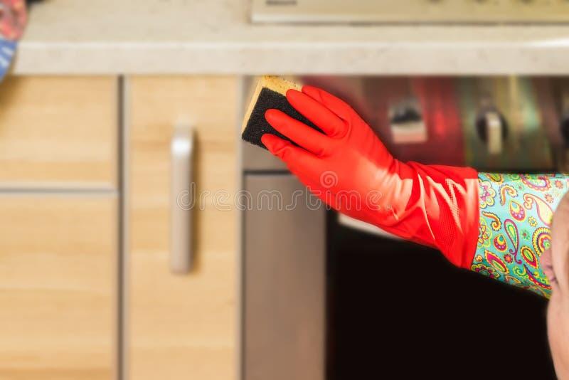 A mulher faz tarefas na cozinha em casa imagens de stock