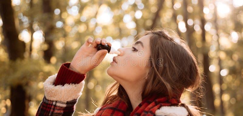 A mulher faz uma cura para a constipa??o comum no parque do outono Mulher nova com len?o O pessoa doente tem o nariz ralo doente imagens de stock