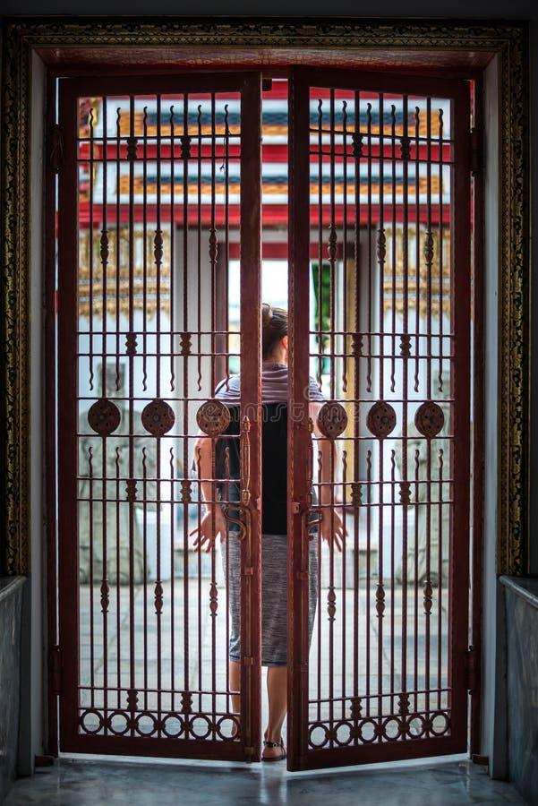 A mulher fecha a porta da porta do ferro atrás dela fotografia de stock