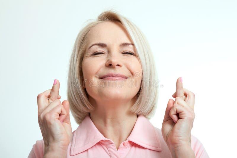 A mulher fechado seus olhos, faz um desejo e uns dedos cruzados imagens de stock