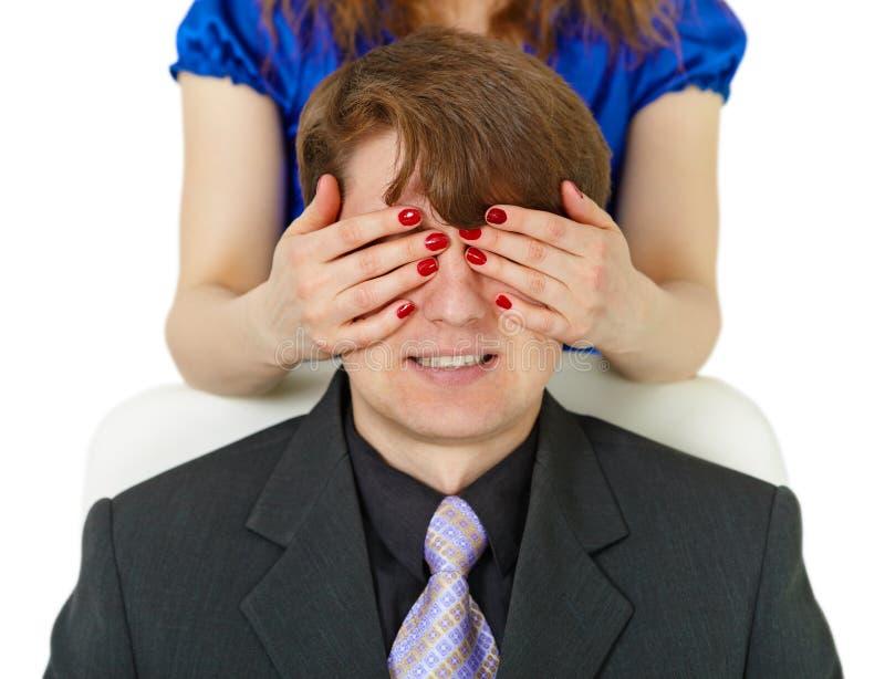 A mulher fechou-se ao homem do olho por meio das mãos fotos de stock
