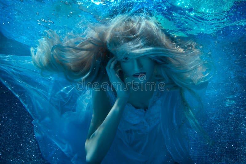 Mulher feericamente sob a água em um vestido branco fotos de stock