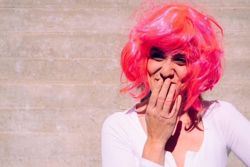 Mulher feia com peruca colorida ridícula e gestos desagradáveis foto de stock
