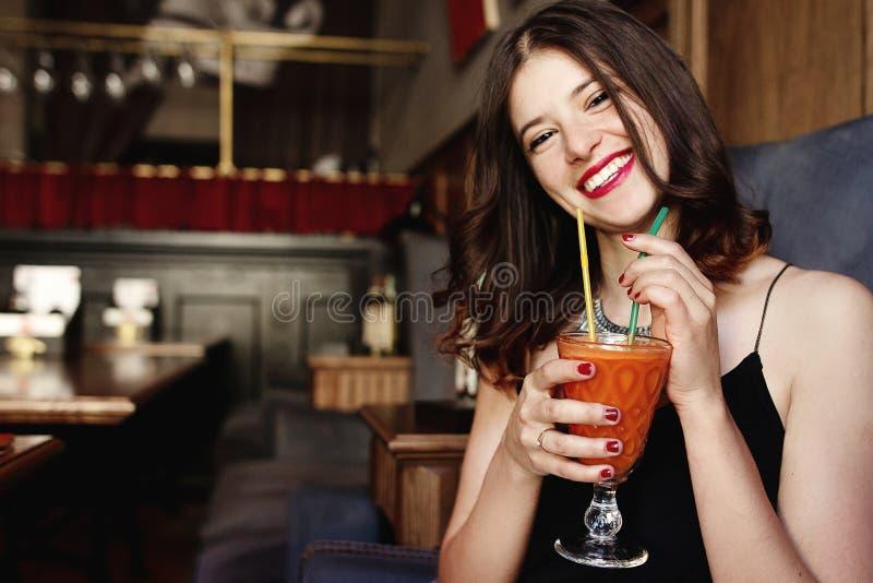 Mulher feliz à moda que guarda o batido fresco da cenoura deliciosa e imagens de stock royalty free