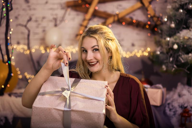 A mulher feliz abre um presente na véspera do ` s do ano novo fotos de stock