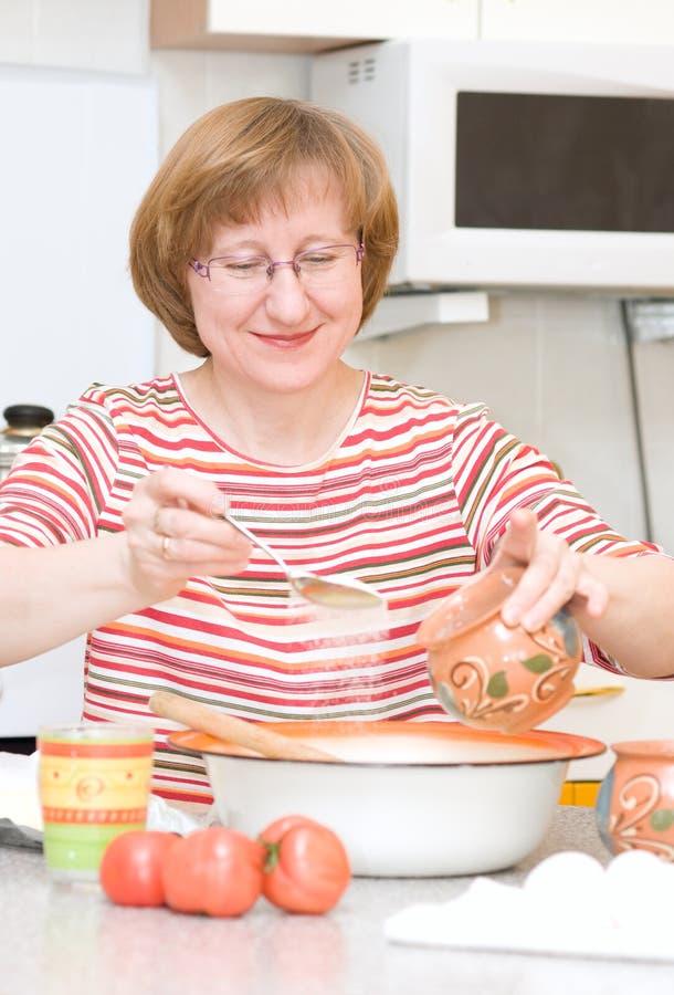 A mulher feliz adiciona o açúcar em uma bacia fotos de stock